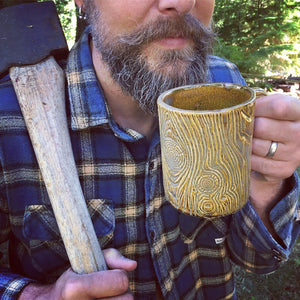 bearded woodsman with ax drinking out of a pottery mug that looks like a wooden mug or beer stein