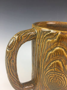 detail image of lumberjack mug showing wood texture, carved into clay