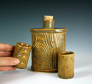 lumberjack flask shown with matching shot glasses, pottery carved to look like woodgrain