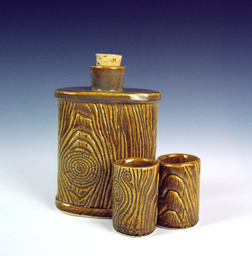 lumberjack pottery flask shown with shot glasses. carved to resemble woodgrain