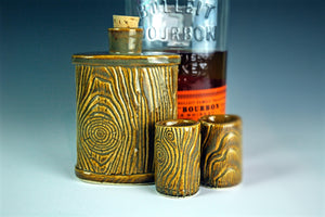 pottery lumberjack flask shown with shot glasses and bourbon