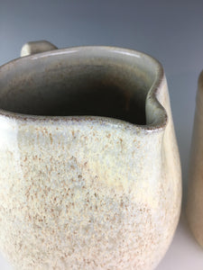 detail shot of pottery pitcher showing the spout of the pitcher and the way the speckled white glaze allows the red clay to show through at the etdges