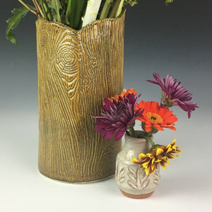carved bud vase shown with daisies. woodgrain vase shown in background.