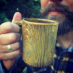 Lumberjack, bearded man drinking out of a pottery mug, carved with woodgrain to imitate tree texture