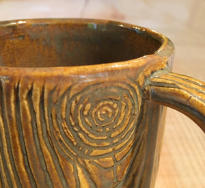 close up detail of woodgrain carving on pottery mug