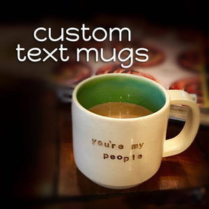 Customized text on a handcrafted, wheel  thrown coffee mug. (text reads: Custom text mugs. Mug reads: you're my people)