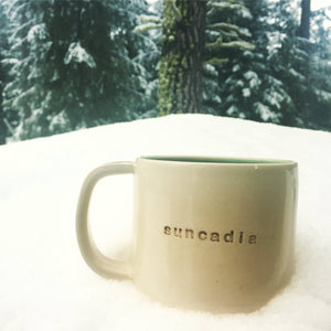 customized text mug sitting in the snow (mug reads: suncadia)