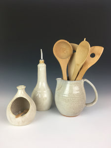 pottery kitchen set in speckled white. salt cellar with bamboo spoon, olive oil cruet, pottery pitcher, shown here being used as a utensil holder. artisan made pottery