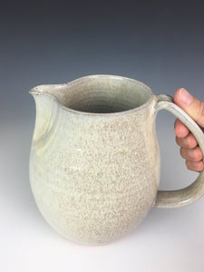 white speckled pottery pitcher with pulled handle. artisan made, wheel thrown  pottery