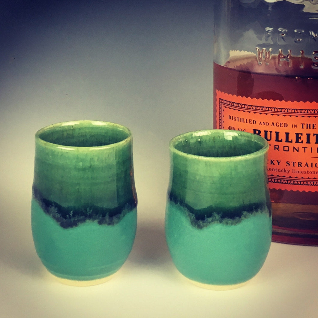 set of two shot galsses in emearld city green glaze. shown with bourbon in background