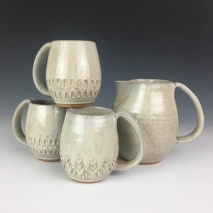 collection of artisan made pottery: carved mugs and speckled white pitcher. red clay with speckled white glaze