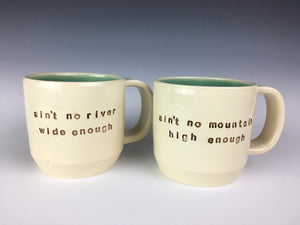 set of customized text mugs. mugs read : ain't no river wide enough / ain't no mountain high enough. white mugs, brown text, green interior