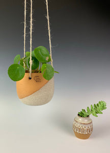 Carved bud vase shown here with matching hanging planter. red clay, white glaze