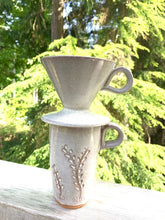 Load image into Gallery viewer, Coffee pour over, wheel-thrown pottery, white glaze with speckles, shown on a travel mug, photographed outside, cedar trees in background