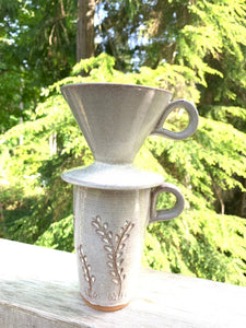 Coffee pour over, wheel-thrown pottery, white glaze with speckles, shown on a travel mug, photographed outside, cedar trees in background
