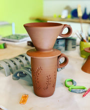 Load image into Gallery viewer, Travel mug and coffee pour over as they are being made in the pottery studio. The red clay is shown before it is glazed or fired. on the work table are handles for more mugs and pottery tools