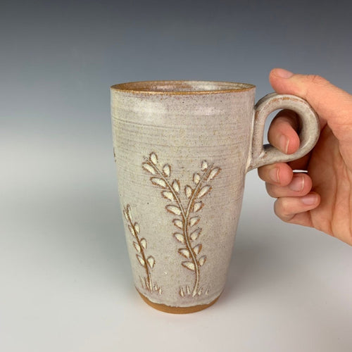 Pottery travel mug with finger loop handle. thrown on the pottery wheel, red clay, carved with vine pattern, white speckled glaze