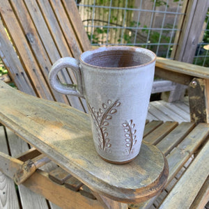 tall latte size travel mug with finger loop handle. vine carvings and white glaze. shown on adirondak chair