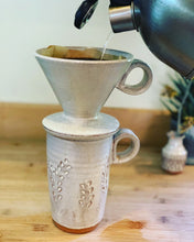 Load image into Gallery viewer, travel mug shown with coffee pour over. both are thrown on the potters wheel in red clay, the mug is carved with a vine pattern and they are glazed in speckled white glaze