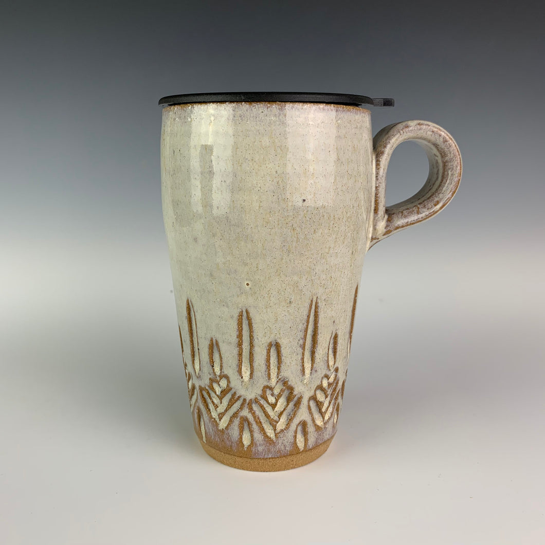 wheel thrown pottery travel mug with tree pattern carved into the bottom half of the mug. shown here with a fitted travel lid