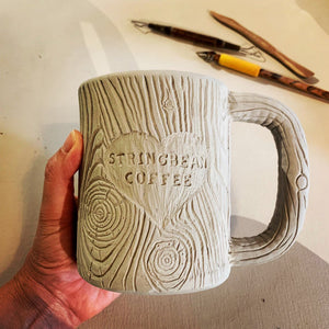 the artist making a woodgrain textured pottery mug with customizable text added. appears as initials carved into a tree trunk, or name in a heart carved into a tree