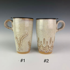 artist made Pottery travel mugs with lids. Mug #1 shows the vine pattern, mug #2 shows a carved tree-like pattern. mugs have finger loop handles so that they fit in cupholders