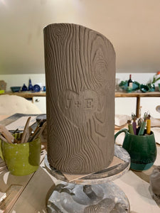 woodgrain textured vase, cylindrical in shape with heart and initials carved into texture. reminiscent of a tree with carved initials