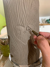 Load image into Gallery viewer, woodgrain textured vase, cylindrical in shape with heart and initials carved into texture. the artist carving a vase that is reminiscent of a tree with carved initials