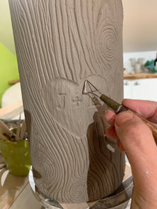 woodgrain textured vase, cylindrical in shape with heart and initials carved into texture. the artist carving a vase that is reminiscent of a tree with carved initials