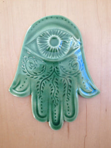 hanging hamsa hand in celadon green with evil eye and vine pattern carved in