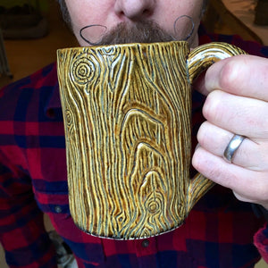 northwest woodsman drinking out of a lumberjack style mug
