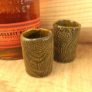 two lumberjack shot glasses, pottery carved to look like woodgrain, shown with a bottle of bourbon