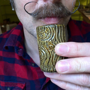 mustachioed man with handlebar mustache drinking from a lumberjack shot glass. pottery shot glass carved to look like wood