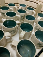 Load image into Gallery viewer, Cedar sprigs pressed into custom mugs, with mottled-green interiors