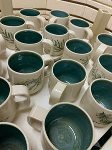 Cedar sprigs pressed into custom mugs, with mottled-green interiors