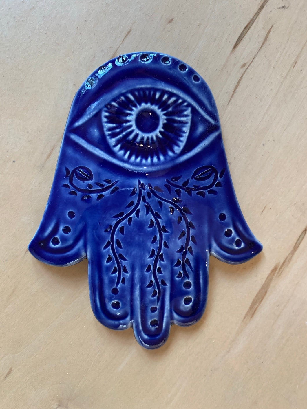 Hamsa wall hanging in cobalt blue with vine patterns carved in. ceramic, approximately 5