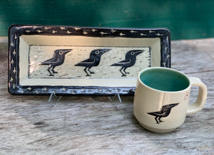 Crow platter, white with black sgraffito carved crow, shown with crow love mug