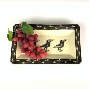 crow or raven carved pottery platter shown with grapes. crows are sgraffito carved into the center with footprints around the edge. stoneware, black on white clay.