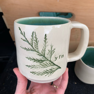 a custom handcrafted mug with a Cedar branch impressed into the side. the interior is glazed in a matching green