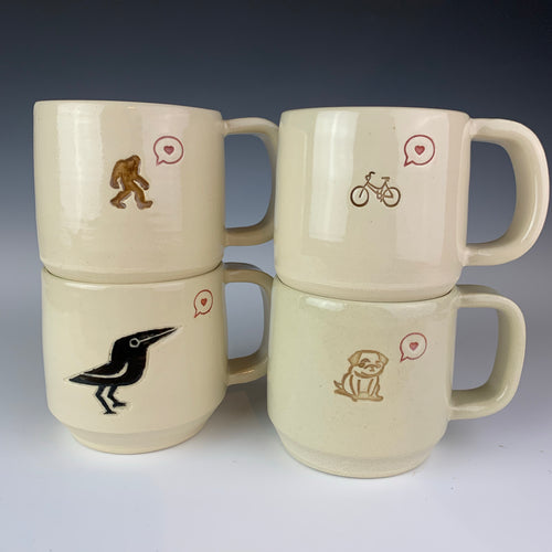 Love mugs. Versions shown are sasquatch love, bike love, pug love, and crow love. Each mug is thrown on the potters wheel, then has a handcrafted handle added.