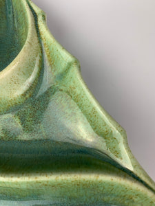 detail image of speckled green glaze on christmas tree candy dish. mossy green with brown speckles pooling where melted