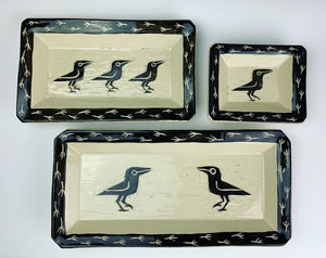 three rectangular pottery platters with crow designs carved in them. sgraffito carving of crows/ravens in center and corvid footprints around the edges.