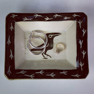 small crow catch all tray holding rings, and earrings, shiny things. rectangular tray, sgraffito crow carving with corvid footprints around the edges.