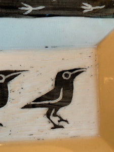 detail shot of crow carving in a pottery platter, texture is shown