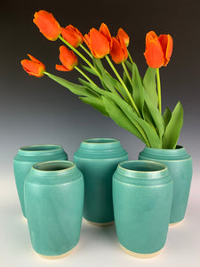 turquoise green vases displayed with tulips.