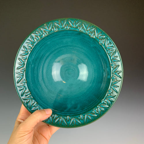 the artist holding a stoneware bowl with a hand carved rim. This bowl is glazed in teal