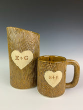 Load image into Gallery viewer, lumberjack, woodgrain appearance on pottery mug and vase. with heart and initials custom carved into surface