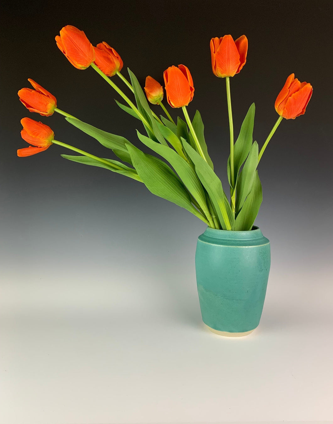 turquoise green vase displayed with tulips