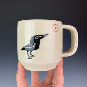 Crow love mug. wheel thrown mug with a crow painted and carved in, and a heart in a speech bubble stamped and glazed with red.