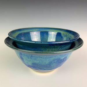 two wheelthrown blue world bowls nesting. the bowls are glazed in cobalt blue with turquoise green glaze melting down into the blue from the rim of the bowls.